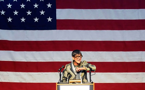 Rosa DeLauro speaking in front of an American flag